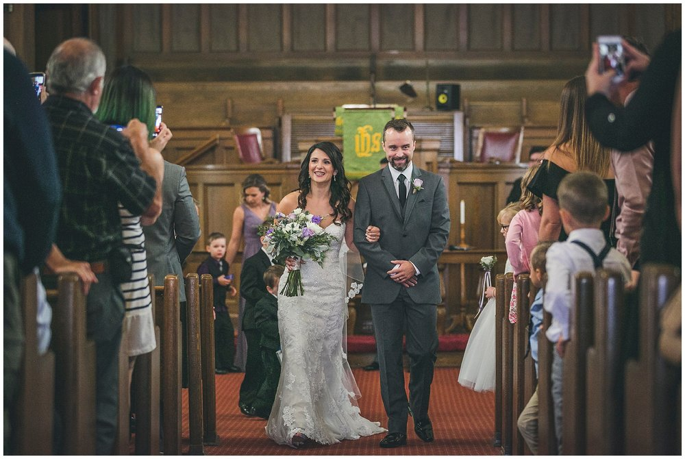 Newly married couple walks down the aisle