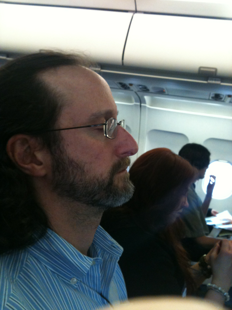 Airplane game: take a covert close-up of the bearded, small stringed instrument-playing man whom Mike covertly photographed in the airport, and who happens to be sitting right next to you, in 25E.