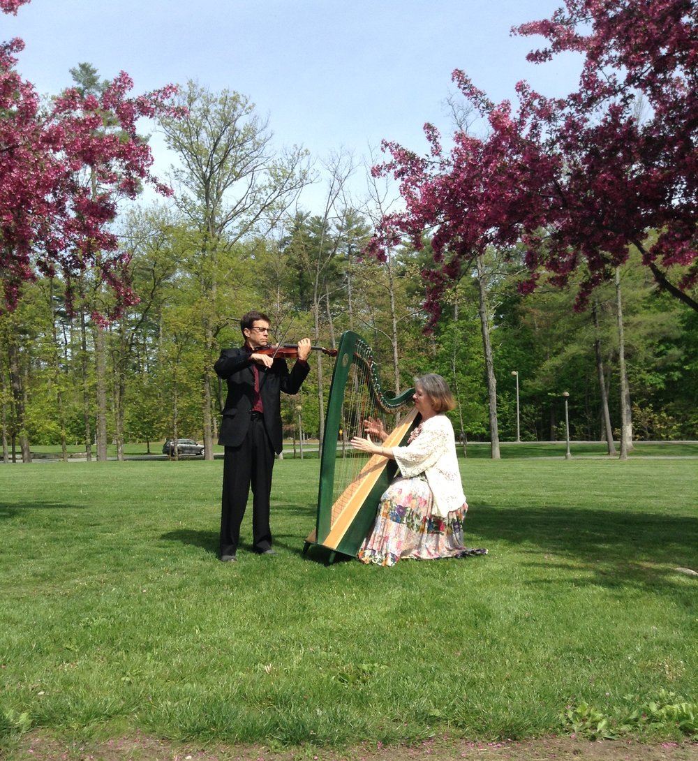 The Starlight Duo perform at an outdoor wedding.