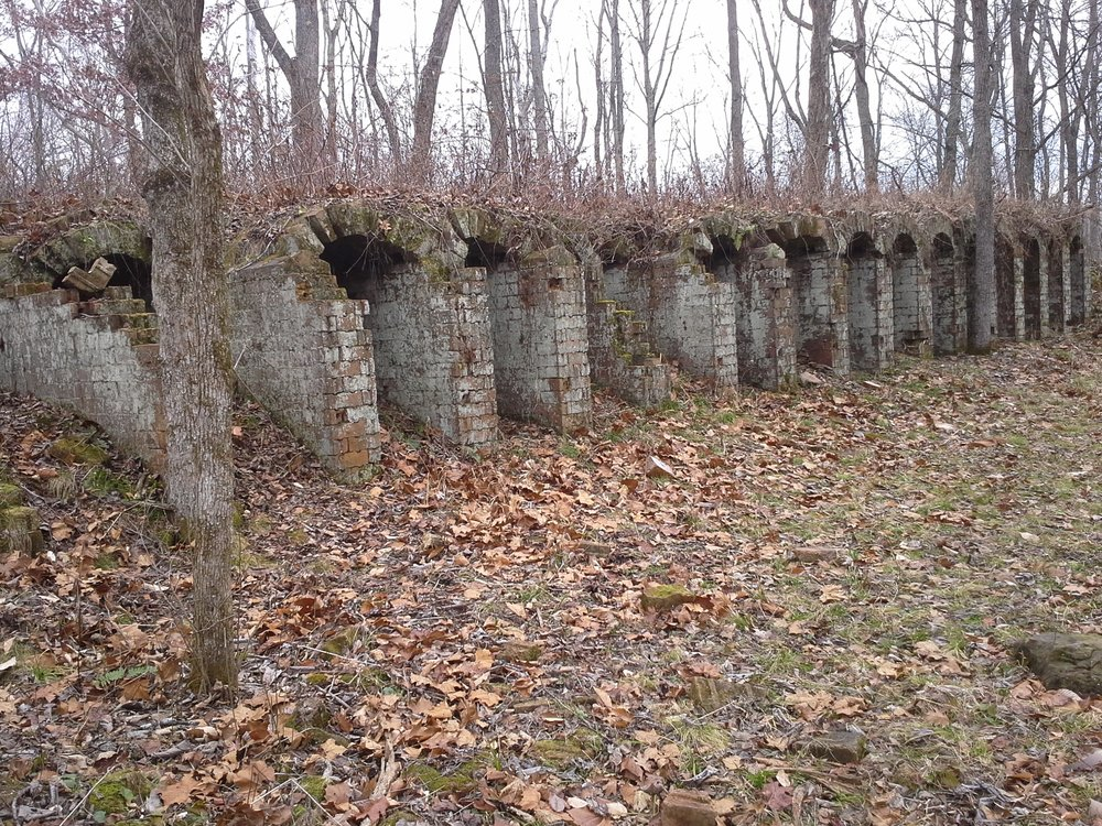 The last standing example in the world of Belgian Coke Ovens imported first to PA, then to a location in what is now the  Vinton Experimental Forest  near Dundas, OH. Each stone is hand crafted and numbered for re-assembly. Labeled as Vinton Furnace, it was never very successful and fell into disrepair. It is difficult to access, and a bit of a challenge to find, but well worth the adventure. Take  Stone Quarry Rd  (very rough gravel) south of Hwy 50, past the closed end of  Murphy Rd  (not closed to adventure riders - but quite a challenge, especially in wet or icy conditions), and park by the rotten bridge. Follow trail signs and pray. Better, use GPS -  N 39° 12.296 W 082° 24.444