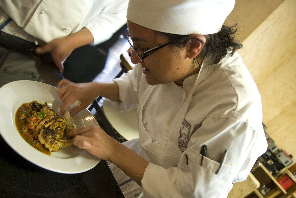 Student Nina Justamonte of the Culinary Centre of Monterey adds the finishing touches to a game hen on 20 March 2008.