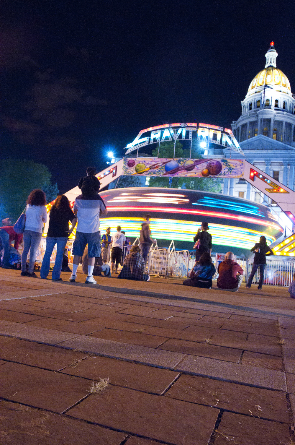 The Taste of Colorado winds down in front of the Colorado State Capitol as the festival's rides spin the last of their riders. The yearly festival brings huge crowds to Denver's heart over Labor Day weekend.