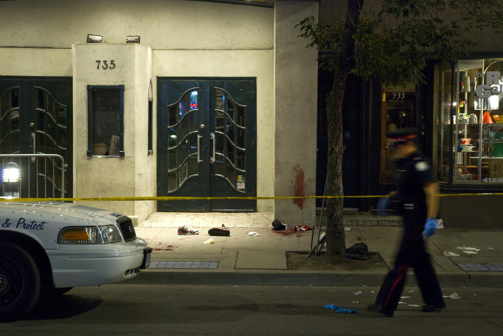 A Toronto Police Service officer walks past the scene of a stabbing which occurred outside the Opera House concert hall at Broadview and Queen West on August 6, 2009.  Two men were taken to the hospital with serious injuries.