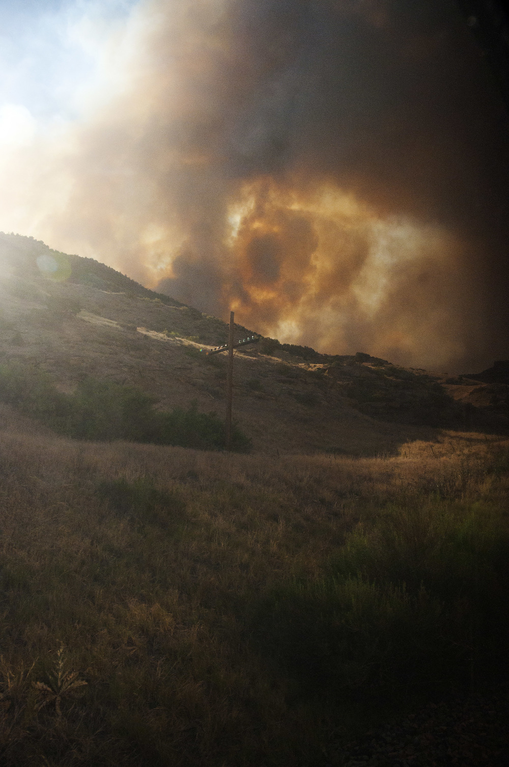 The Pine Ridge fire burns down into De Beque Canyon near Grand Junction, CO on 28 June 2012. The fire, seen here from an Amtrak train, shut down both the railway line and Interstate 70 for hours until the wind pushed it back atop the surrounding mesa.