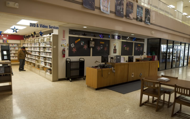 A patron takes a look at the Gary Library's collection of video media on its last day of operation.