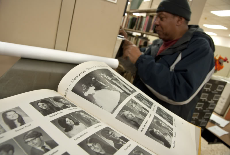 Rufus Purnell looks through the Indiana Room's collection of high school yearbooks. His photo appears in the book in the foreground, on the top row of the left page, near the fold.