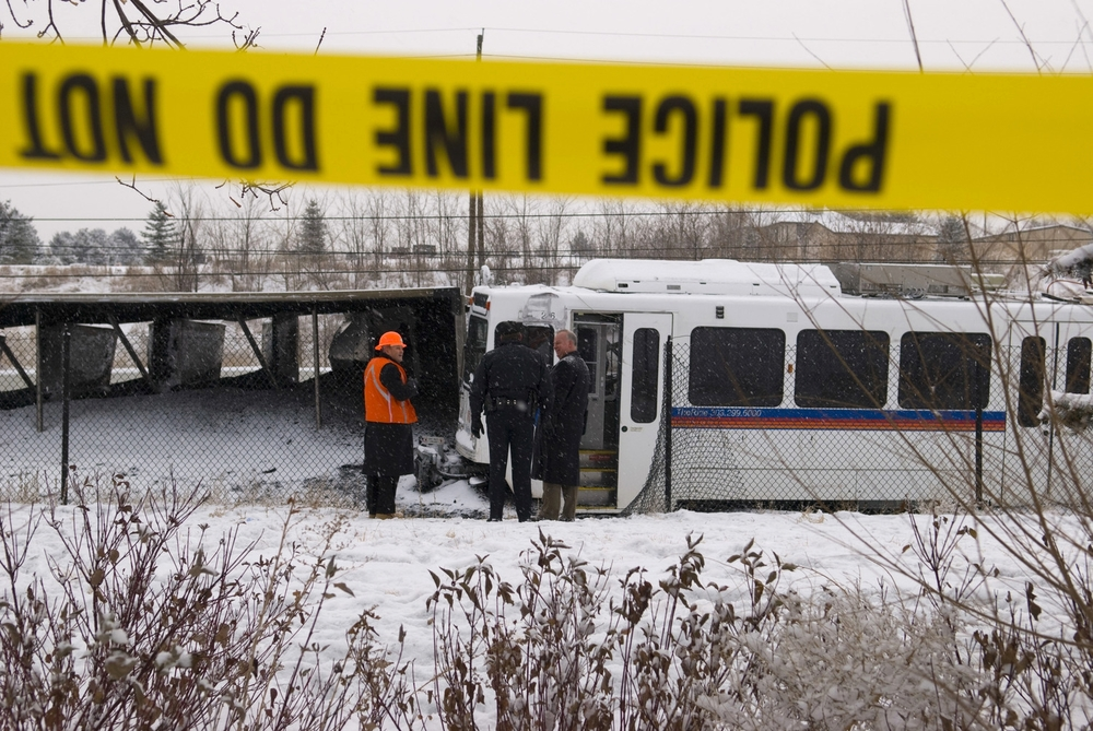 Littleton Police investigators and Union Pacific workers survey the carnage after an RTD light rail train collided with an overturned Union Pacific coal train in Littleton on 11 December 2007.