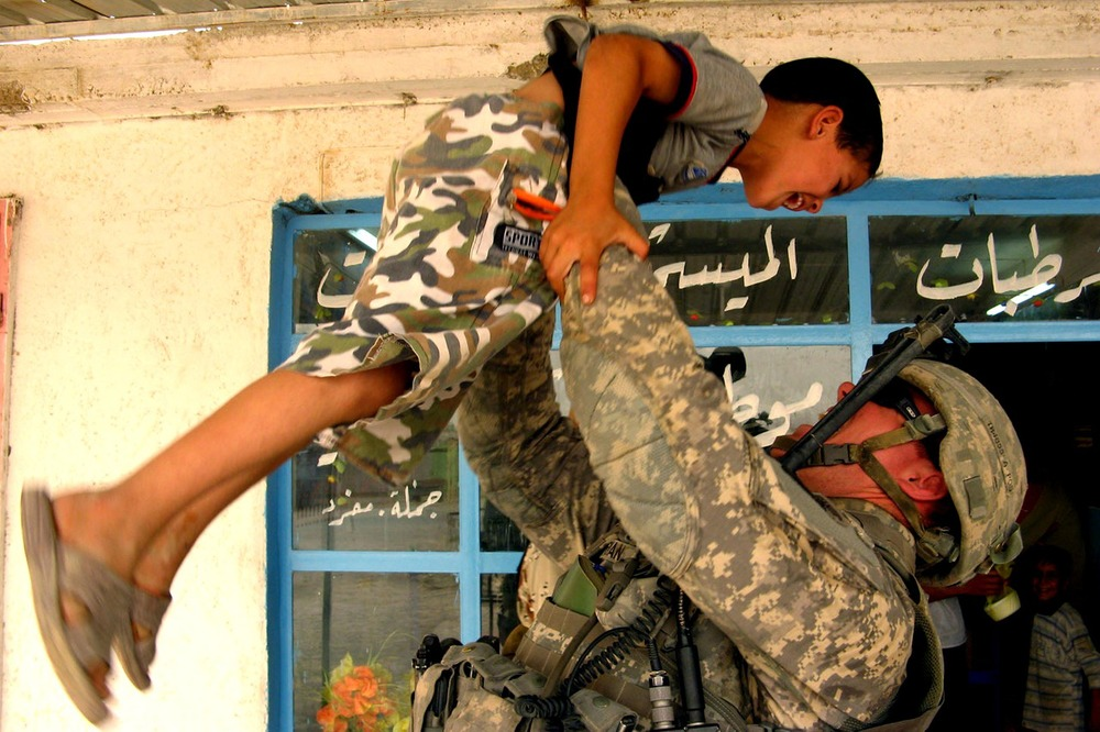 Soldier interacting with a boy in the Middle East
