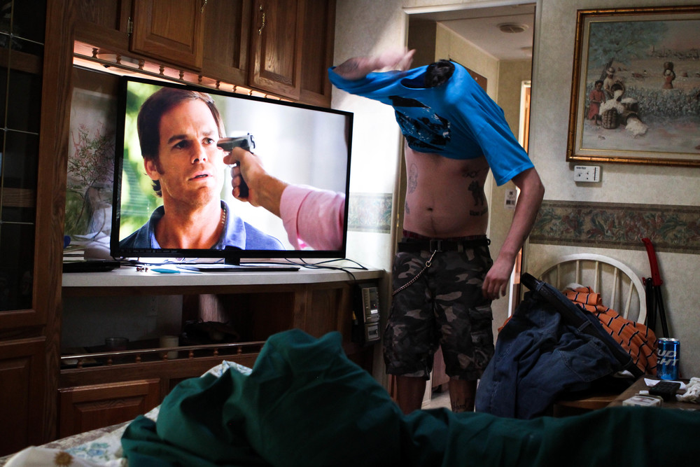 Ryan struggles to get his shirt on by himself while his father watches Dexter on the pullout couch in the camper.