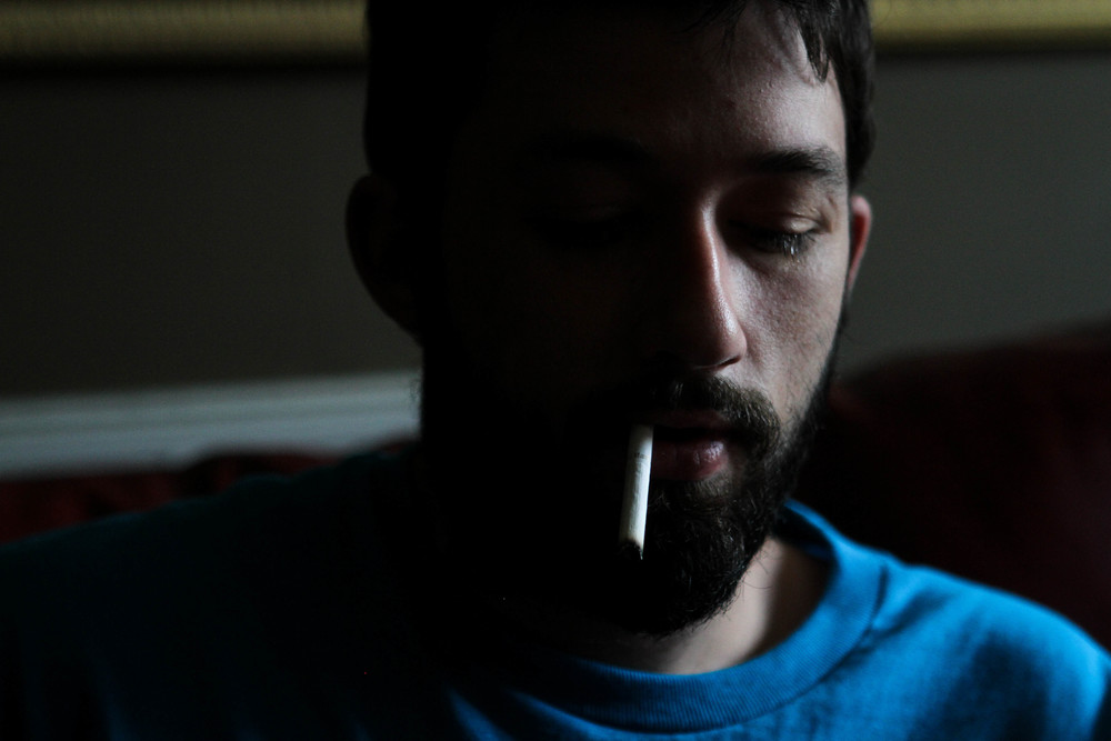 Ryan smokes on a couch in his mother's living room.