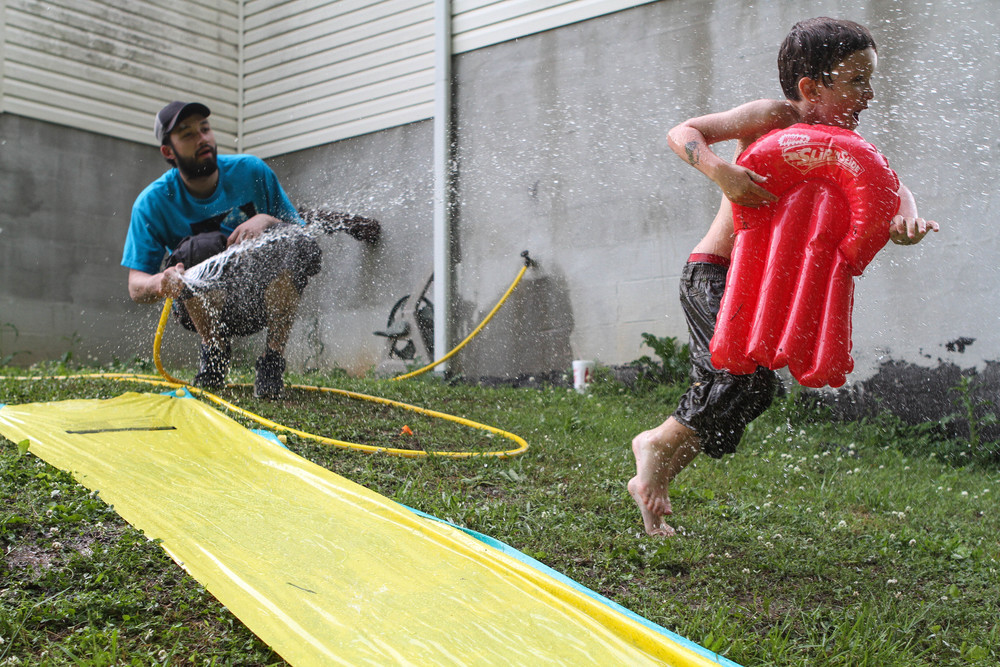 Ryan diverts the hose from the slip-and-slide to splash his son Malachi, in the backyard of his mother's house. She has custody of the boy, although Ryan visits often.