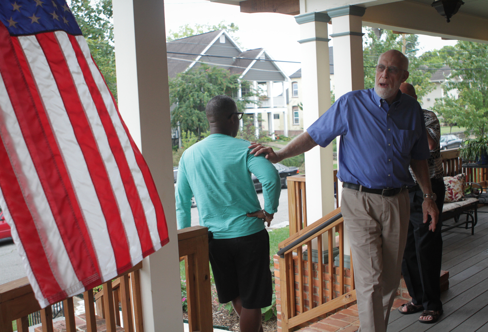 Tresa McCallie holds Moses Freeman's hand during the welcoming before a potluck dinner at the McCallie home on May 2.