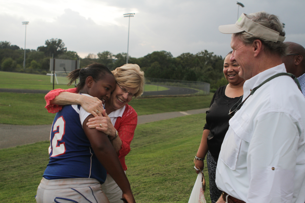 Suzy Baggett hugs Lauren Abramson after her softball game as Curtis Baggett and Lauren's parents, Kimberly and Charles Abramson, look on at Cleveland Middle School on Sept. 15, 2014.