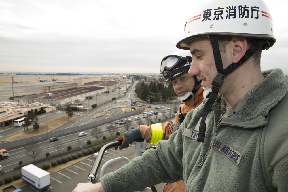 (Left to right) Airman 1st Class Steven Taylor, 374th Civil Engineer Squadron firefighter, and Yuki Yoshizawa, Tokyo Fire Department Fussa Fire Station firefighter, are elevated 100 feet by a Tokyo FD fire ladder truck, during the safety festival at Yokota Air Base, Japan, March 6, 2015. The 374th Airlift Wing Safety Office provided Yokota residents with various events such as the Tokyo Metropolitan Police Department motorcycle unit demonstration, traffic safety demonstration, earthquake and smoke house, firefighting experience, fire ladder trucks experience, 374th Security Forces Squadron patrol vehicle ride, seatbelt simulator and child car seat checks. (U.S. Air Force photo by Osakabe Yasuo/Released)