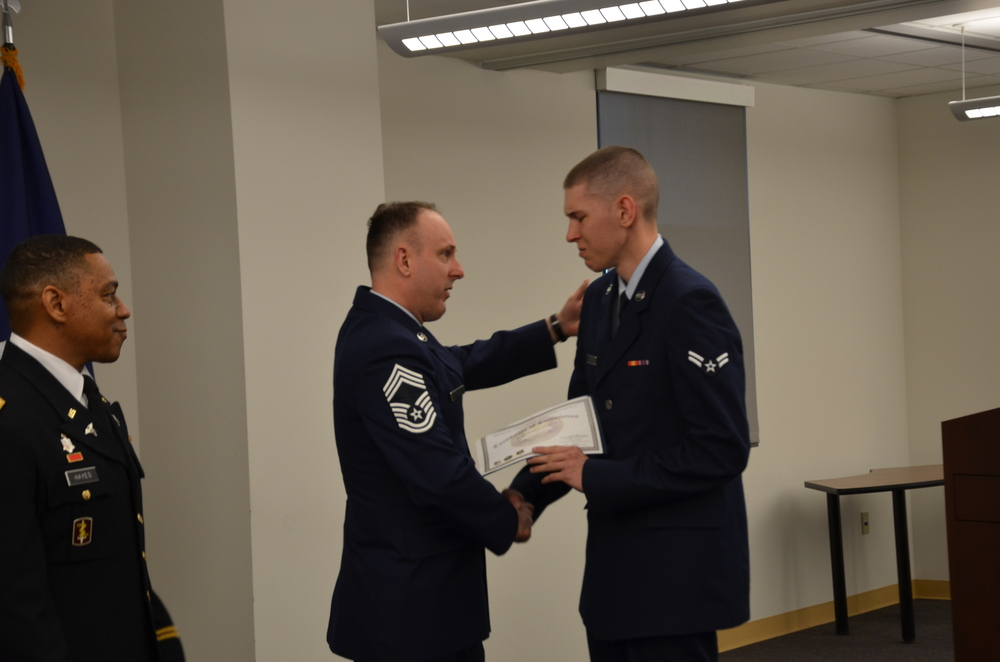 Chief Master Sgt. Charles Frizzell presents his son, Airman Christian Frizzell, with his graduation certificate during his Biomedical Equipment Technician class graduation ceremony April 10 at the Medical Education and Training Campus. Airman Frizzell is starting his new career at Wright-Patterson Air Force Base, Ohio. His father, also a BMET, is currently assigned as the senior enlisted advisor to the commander at the 374th Medical Group at Yokota Air Base, Japan. (Photo by Lisa Braun)