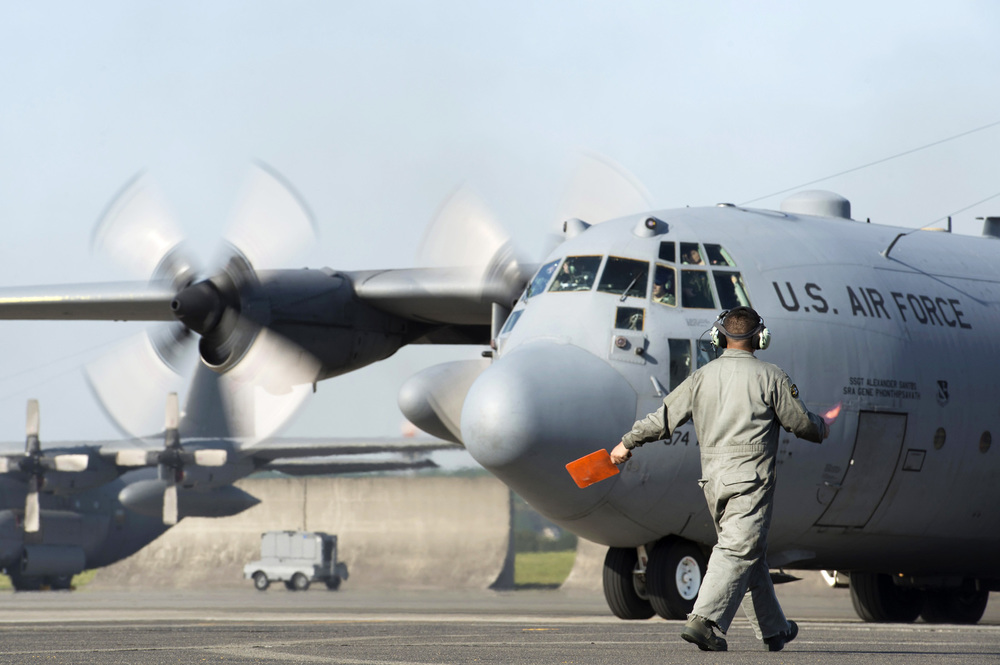 A crew chief with the 374th Aircraft Maintenance Squadron, guides a C-130 Hercules to the taxiway at Yokota Air Base, Japan, May 5, 2015. Members of Yokota left to provide humanitarian airlift and relief operations to support the U.S. Agency of International Development and the Government of Nepal in response to the 7.8 magnitude earthquake that devastated the country April 25, 2015. (U.S. Air Force photo by Staff Sgt. Cody H. Ramirez/Released)