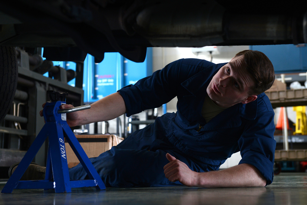 Senior Airman Brandon Higginbotham, 374th Logistics Readiness Squadron vehicle maintenance journeyman, places jack stands under a government vehicle at Yokota Air Base, Japan, April 28, 2015. Stands are placed to ensure the safety of the mechanics working on vehicles. (U.S. Air Force photo by Airman 1st Class David C. Danford/Released)