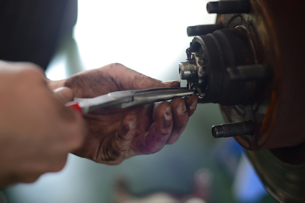 Senior Airman Brandon Higginbotham, 374th Logistics Readiness Squadron vehicle maintenance journeyman, removes a cotter pin from the rotor hub assembly while conducting scheduled vehicle maintenance at Yokota Air Base, Japan, April 28, 2015. Cotter pin tines are bent around the bolt to provide a secure connection within the assembly. (U.S. Air Force photo by Airman 1st Class David C. Danford/Released)