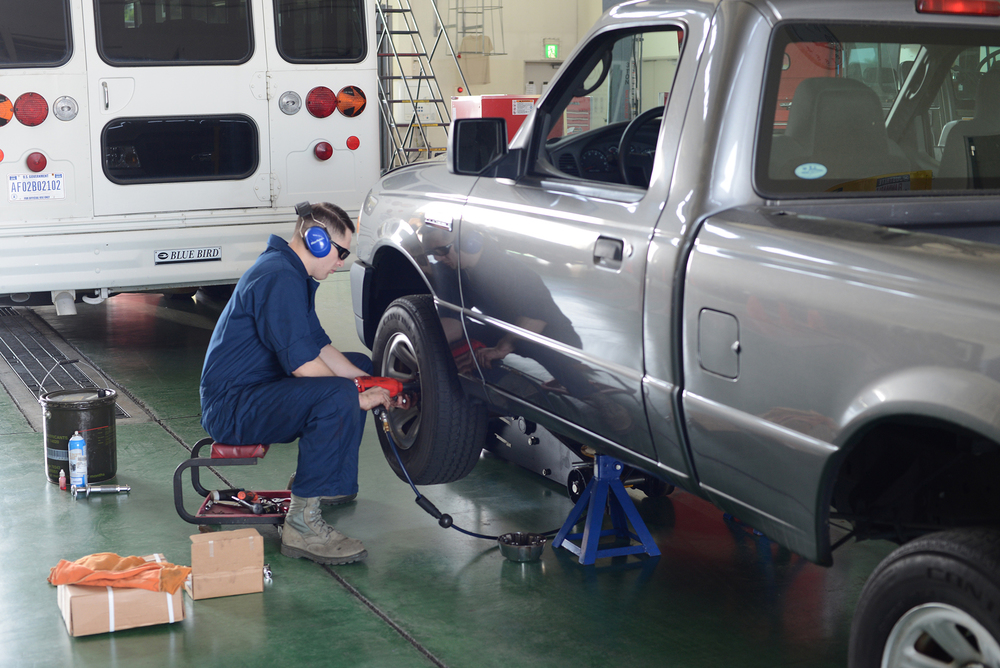 Senior Airman Brandon Higginbotham, 374th Logistics Readiness Squadron vehicle maintenance journeyman, removes a wheel from a government vehicle at Yokota Air Base, Japan, April 28, 2015. The truck was brought into the vehicle maintenance shop to troubleshoot the front brakes. (U.S. Air Force photo by Airman 1st Class David C. Danford/Released)