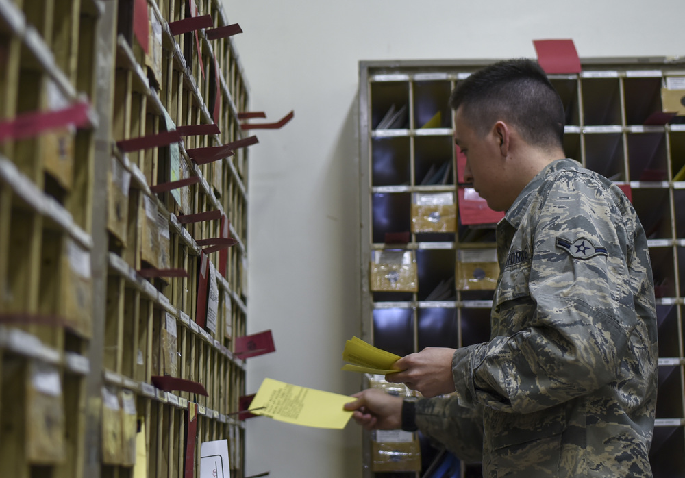 Airman Tristan Dobbins, 374th Communication Squadron Post Office postal clerk, drops off yellow delivery slips into mailboxes at Yokota Air Base, Japan, June 15, 2015. Dobbins estimates that they drop off 200 to 300 slips per day. (U.S. Air Force photo by Senior Airman Michael Washburn/Released)