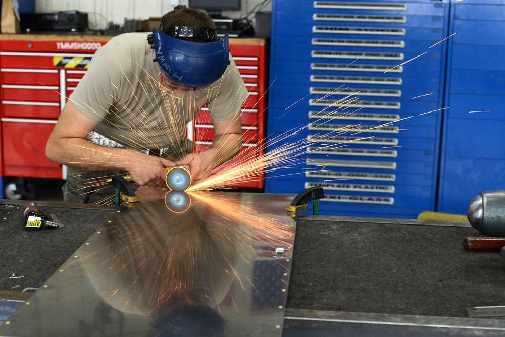 Airman 1st Class Jordan Pontius, 374th Maintenance Squadron aircraft structural maintainer, trims a steel cabinet door June 15, 2015, at Yokota Air Base, Japan. The door is a custom made project for the base hospital. (U.S. Air Force photo by Senior Airman Desiree Economides/Released)