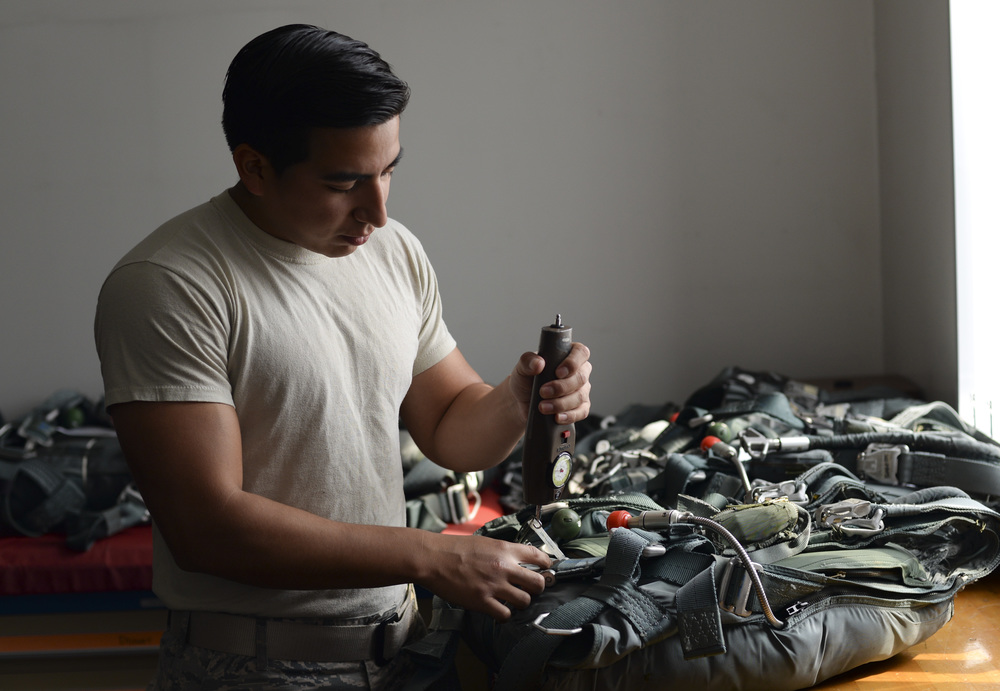 Staff Sgt. David Gutierrez, 374th Operations Support Squadron aircrew flight equipment supervisor, uses a torque device to measure the resistance of a parachute backpack clamp at Yokota Air Base, Japan, June 16, 2015. The backpacks need to be inspected every 30 days to ensure they are of the highest standard to keep the aircrew safe. (U.S. Air Force photo by Senior Airman Michael Washburn/Released)