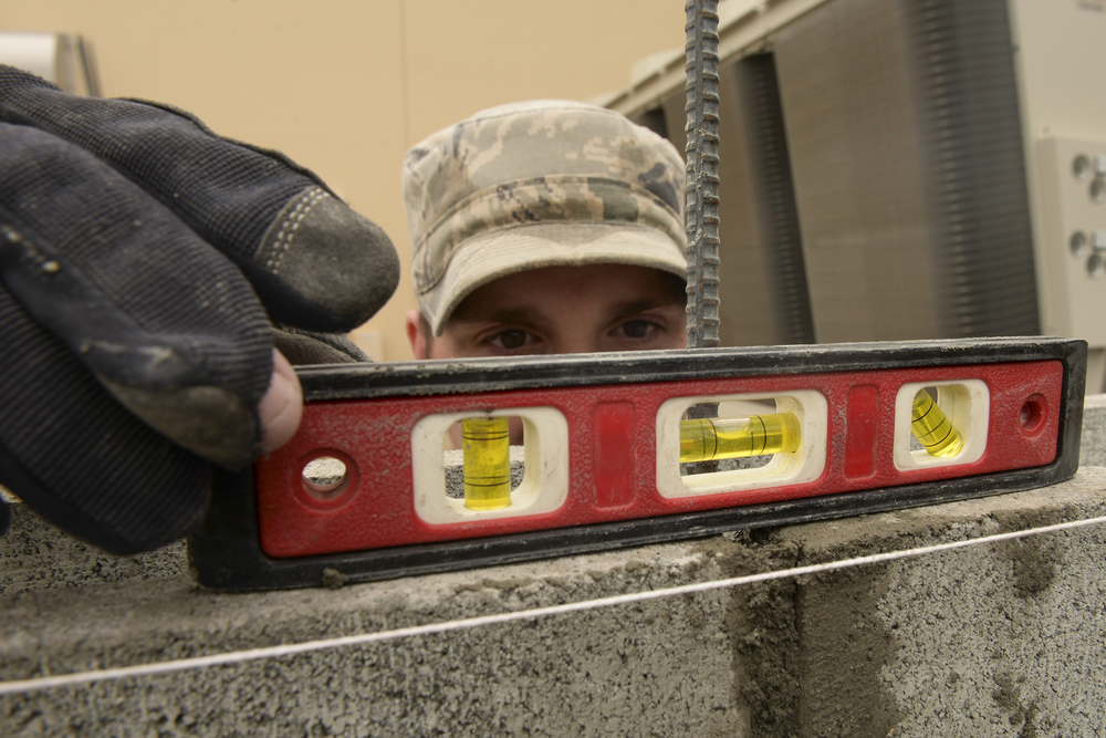 Airman 1st Class Tristan Fournier, 374th Civil Engineer Squadron structural journeyman, uses a level to test the placement of a cinder block he has just laid at Yokota Air Base, Japan, June 16, 2015. The 374 CES structural Airmen support Yokota by building, sustaining, and maintaining structures on base. (U.S. Air Force photo by Airman 1st Class Elizabeth Baker/Released)