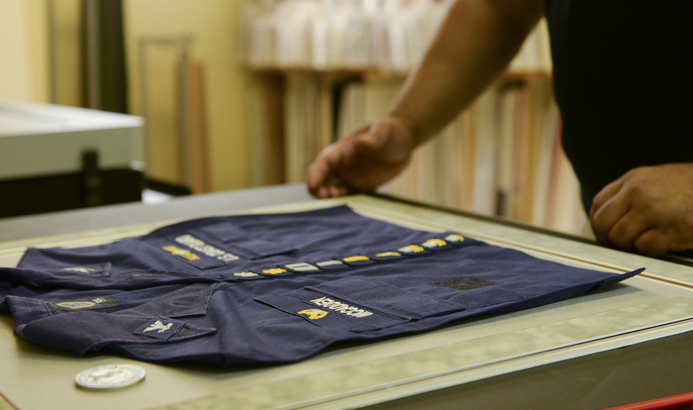 Robert Peche, Arts and Crafts Center Frame Shop picture framer, secures a commemorative uniform piece to a matt board at Yokota Air Base, Japan, June 17, 2015. The frame shop helps to honor military careers by creating a variety of commemorative objects such as shadow boxes and framed photos. (U.S. Air Force photo by Airman 1st Class Elizabeth Baker/Released)