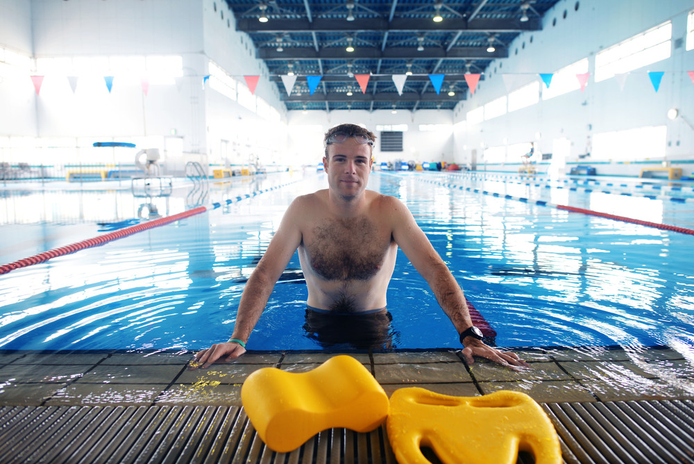 Navy Lt. Chadwick Shroy, a United States Forces Japan intelligence officer, poses in a swimming pool June 16, 2015, at Yokota Air Base, Japan. Shroy was performing physical training to ensure he's fit to flight. (U.S. Air Force photo by Airman 1st Class Delano Scott/Released)