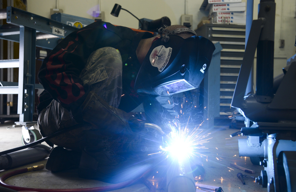 Airman 1st Class Curtis Doherty, 374th Maintenance Squadron aircraft metals technology journeyman, welds a hole on a tow bar on a B-1 platform at the fabrication shop at Yokota Air Base, Japan, June 23, 2015. The metal technology shop performs maintenance work with welding and machining equipment to keep aircraft in flight and repair equipment for various base agencies. (U.S. Air Force photo by Senior Airman David Owsianka/Released)