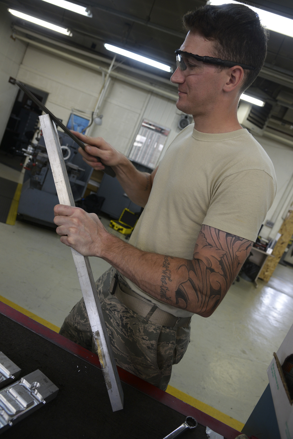 Senior Airman Justin Weeks, 374th Maintenance Squadron aircraft metals technology journeyman, smoothens the edge of a metal piece in the fabrication shop at Yokota Air Base, Japan, June 23, 2015. The shop often receives C-130 Hercules exhaust pipes to repair utilizing the technicians' grinding and welding skills. (U.S. Air Force photo by Senior Airman David Owsianka/Released)