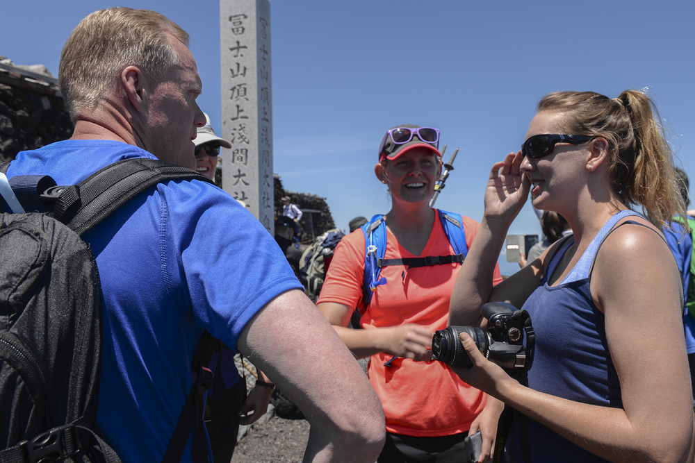 Chief Master Sergeant of the Air Force James A. Cody interacts with Airmen at the summit of Mount Fuji, Japan, July 11, 2015. Cody spent time getting to know many of the hikers, taking time to pose for pictures, sign walking sticks and talk to the Airmen. (U.S. Air Force photo by Airman 1st Class Elizabeth Baker/Released)