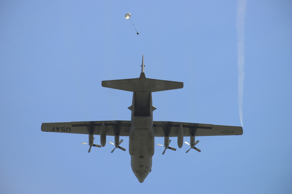 Members of the 36th Airlift Squadron release a sandbag with a parachute from a C-130 Hercules during a training exercise at Yokota Air Base, Japan, July 14, 2015. This exercise tested the squadron's ability to accurately drop cargo to a specific target. (U.S. Air Force photo by Senior Airman David Owsianka/Released)