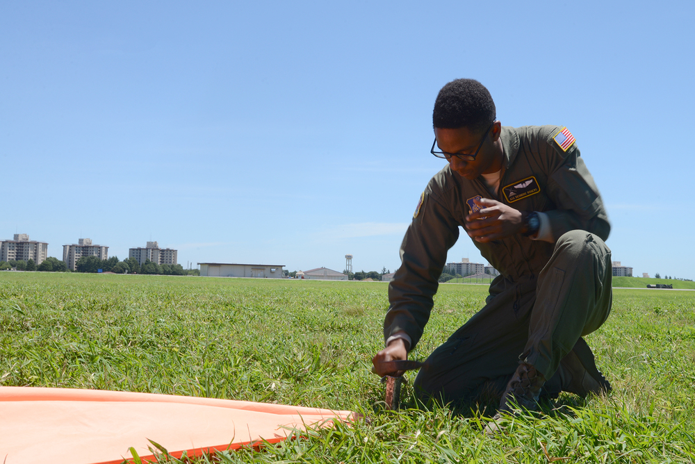 Airman 1st Class Deondre Rogers, 36th Airlift Squadron loadmaster, sets up a raised angle marker on a drop zone in Yokota Air Base, Japan, July 14, 2015. The RAM provides a visible target for C-130 Hercules aircrew to aim for when dropping bundles. (U.S. Air Force photo by Airman 1st Class David C. Danford/Released)