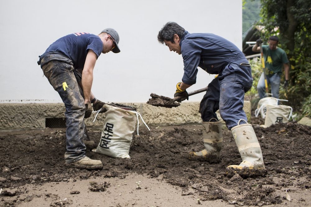 (Left to right) Airman 1st Class Zachary Schofield and Masanobu Ishikawa, both from the 374th Civil Engineer Squadron fire department, clean mudflow from a house at Kanuma City, Tochigi Prefecture, Japan, Sept. 15, 2015. Sixty Airmen and civilians from the 374th CES volunteered to help at sites in the Kasono area in support of floods and landslides caused by the heavy rainfall associated with the post-tropical remnant of Tropical Storm Etau, which stalled over eastern Ja-pan, dumping up to 17 inches of rain in 24 hours, from Sept. 10 to Sept. 11. (U.S. Air Force pho-to by Osakabe Yasuo/Released)