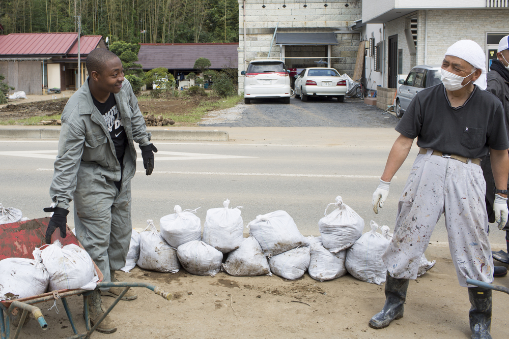 Tech. Sgt. Abdul Smith, 374th Civil Engineer Squadron, carries bags full of mud alongside a local resident at Kanuma city, Tochigi Prefecture, Japan, Sept. 15, 2015. Sixty Airmen and civil-ians from the 374th CES volunteered to help at sites in the Kasono area in support of floods and landslides caused by the heavy rainfall associated with the post-tropical remnant of Tropical Storm Etau, which stalled over eastern Japan, dumping up to 17 inches of rain in 24 hours, from Sept. 10 to Sept. 11. (U.S. Air Force photo by Osakabe Yasuo/Released)