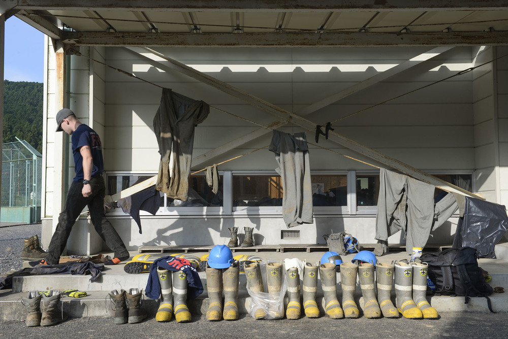 A volunteer with the 374th Civil Engineer Squadron fire protection services searches for his boots early in the morning outside the gym of an elementary school at Kanuma City, Tochigi prefecture, Japan, Sept. 15, 2015. The volunteers, more than 60 Airmen and Japanese who work at Yokota Air Base, helped remove thousands of pounds of mud from the many businesses, buildings and personal homes that were damaged during floods and landslides in the Tochigi area. (U.S. Air Force photo by Staff Sgt. Cody H. Ramirez/Released)