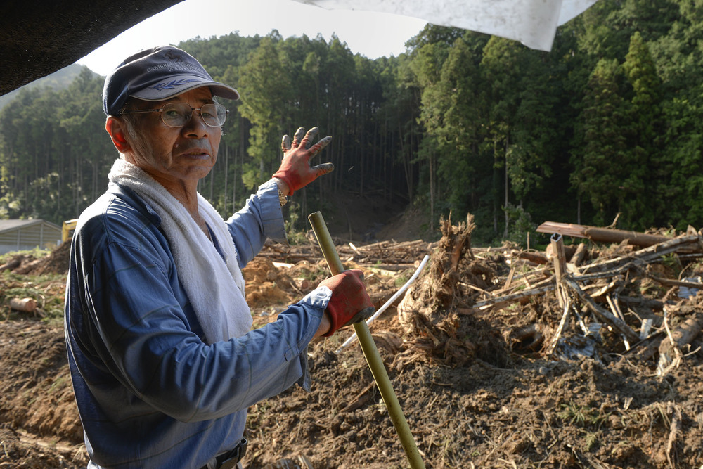 Sota Watanabe, a local farmer, explains how a landslide destroyed much of his property at Kanuma City, Tochigi prefecture, Japan, Sept. 15, 2015. More than 60 volunteers, Airmen and Japanese workers from Yokota Air Base, spent three days helping farmers remove mud and debris from their fields and irrigation systems and cleaning yards and driveways for elderly citizens. (U.S. Air Force photo by Staff Sgt. Cody H. Ramirez/Released)