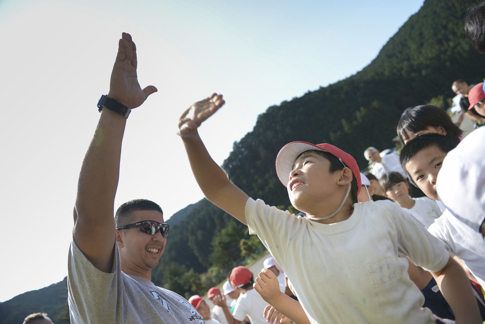 A volunteer from Yokota Air Base raises his hand high above local students after a 'thank you' presentation at Kanuma City, Tochigi Prefecture, Japan, Sept. 15, 2015. More than 60 Airmen and Japanese who work at Yokota Air Base to help remove thousands of pounds of mud from the many businesses, buildings and personal homes that were damaged during floods and landslides in the Tochigi area. Students at the local elementary school made a speech and sang a song to thank the volunteers for their efforts in the community. (U.S. Air Force photo by Staff Sgt. Cody H. Ramirez/ Released)