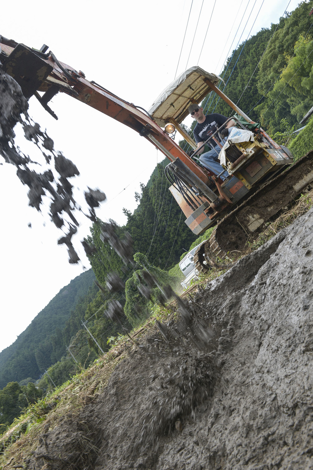 Tech. Sgt. Marshall Johnston, 374th Civil Engineer Squadron structures craftsman, drops mud on the side of an irrigation creek at Kanuma City, Tochigi prefecture, Japan, Sept. 15, 2015. Johnston used mud taken from a clogged irrigation drain to fix an eroded creek wall that was leaking into a farmer's field. More than 60 volunteers from Yokota Air Base ventured to the prefecture to assist with post-flood and landslide relief. (U.S. Air Force photo by Staff Sgt. Cody H. Ramirez/Released)