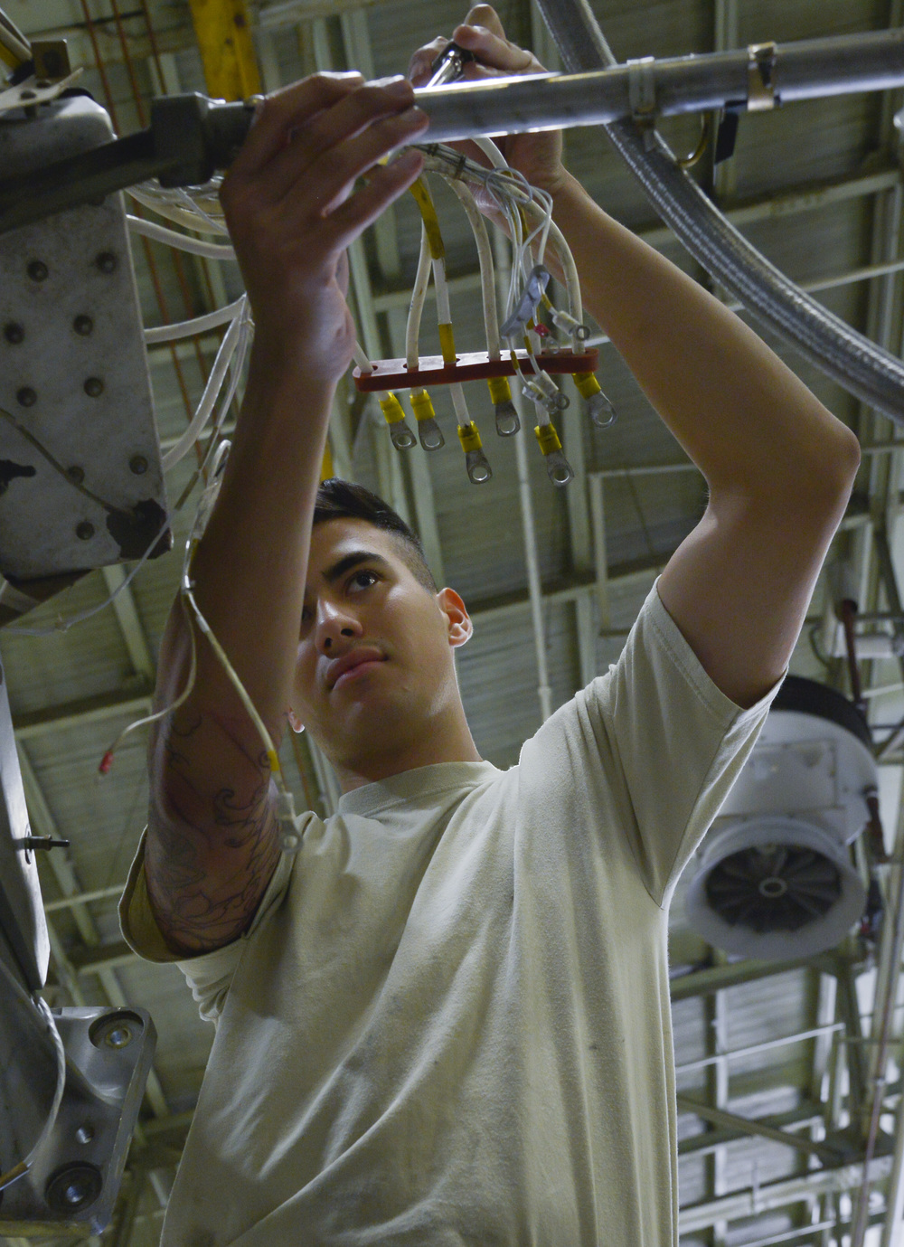 Airman 1st Class Gage Walker, 374th Maintenance Squadron propulsion flight aerospace propulsion apprentice, routes a generator harness on a quick engine change kit at Yokota Air Base, Japan, Sept. 23, 2015. The flight provides engines and propellers for the C-130 Hercules to make sure the aircraft can fly to perform airlift and humanitarian missions throughout the Indo-Asia Pacific Region. (U.S. Air Force photo by Senior Airman David Owsianka/Released)