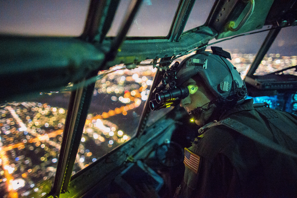 Capt. Thomas Bernard, 36th Airlift Squadron C-130 Hercules pilot, performs a visual confirmation with a night vision goggles during a training mission over the Kanto Plain, Japan, Oct. 14, 2015. Yokota aircrews regularly conduct night flying operations to ensure they're prepared to respond to a variety of contingencies throughout the Indo-Asia Pacific region. (U.S. Air Force photo by Osakabe Yasuo/Released)