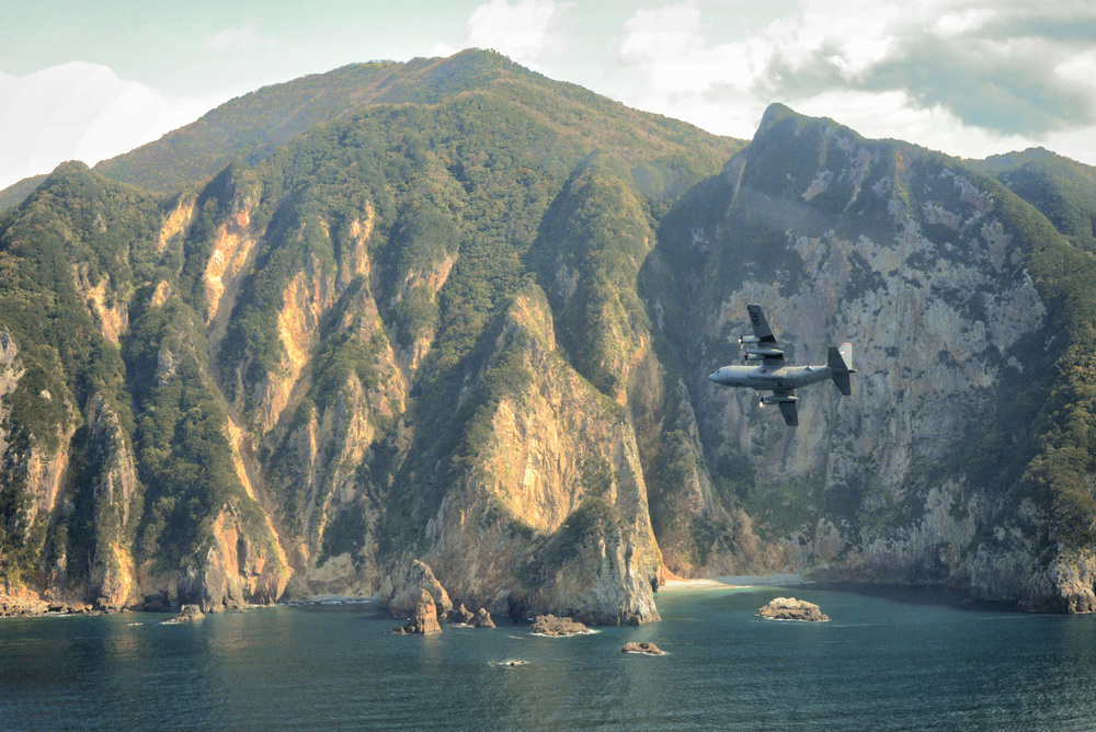 A C-130 Hercules flies over Izu peninsula, Japan, Oct. 14, 2015. Performing regular in-flight operations gives all related personnel real world experience to stay prepared for contingency situations and regular operations. (U.S. Air Force photo by Airman 1st Class Elizabeth Baker/Released)