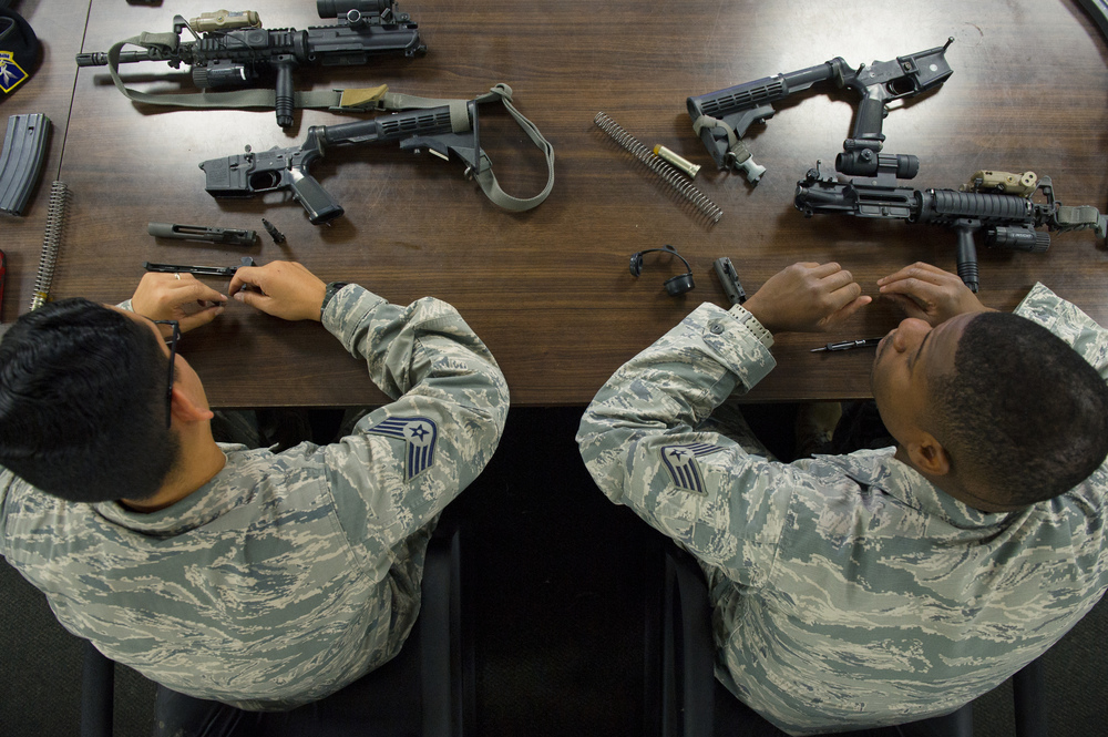 Security Forces Airmen practice disassembling M-4 Carbine assault rifles during a combat arms training class at Yokota Air Base, Japan, Oct. 8, 2015. Practicing proper weapon maintenance is one component of weapons training. (U.S. Air Force photo by Airman 1st Class Delano Scott/Released)
