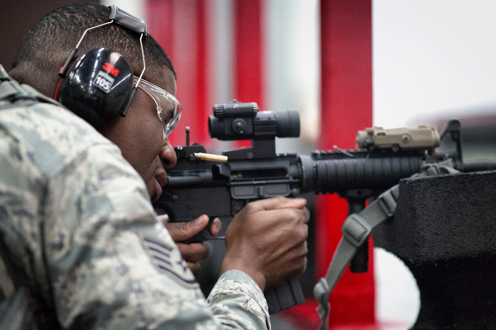 Staff Sgt. Louis Bradshaw, 374th Security Forces Squadron criminal investigator, fires an M-4 Carbine during a qualification test at Yokota Air Base, Japan, Oct. 8, 2015. In order to qualify for deployment in combat arms, each Airman must have at least a score of 44 out of 63 rounds to pass. (U.S. Air Force photo by Airman 1st Class Delano Scott/Released)