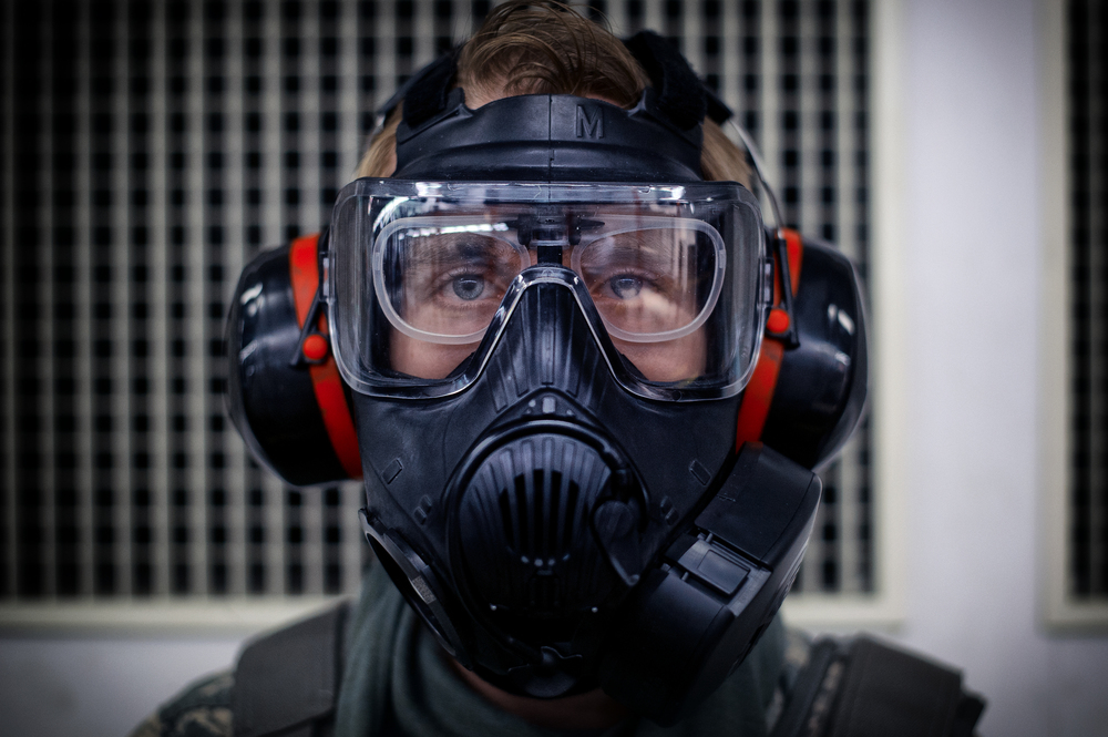 Senior Airman Dylan Fagan, 374th Security Forces Squadron armorer, dons a gas mask before performing M-4 Carbine qualifying at Yokota Air Base, Japan, Oct. 8, 2015. The qualifying course test Airmen on their ability to fire an M-4 carbine from several positions: prone, standing and while wearing a gas mask. (U.S. Air Force photo by Airman 1st Class Delano Scott/Released)