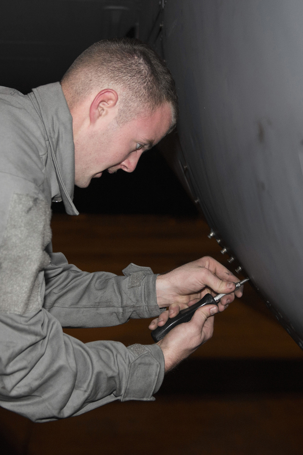 A member of the 374th Aircraft Maintenance Squadron tightens an engine panel on a C-130 Hercules during VIGILANT ACE 16 at Yokota Air Base, Japan, Nov. 2,2015. VIGILANT ACE is a U.S.-Republic of Korea combined exercise aimed at enhancing operational and tactical level coordination through combined and joint combat training. The exercise also provides critical training for the Airmen of the 374th Airlift Wing to maintain peace and stability in Japan and the entire Indo-Asia Pacific region. (U.S. Air Force photo by Staff Sgt. Cody H. Ramirez/Released)