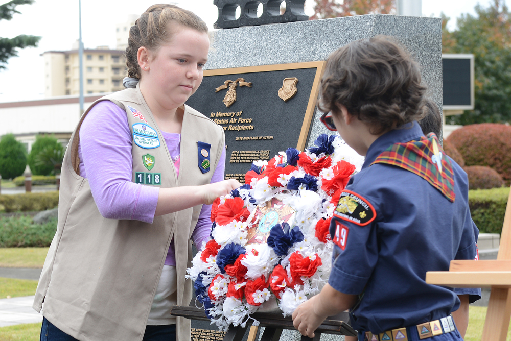 A wreath is placed on an easel by a Boy Scout and Girl Scout at Yokota Air Base, Japan, Nov. 11, 2015. The Boy Scouts of America and Girl Scouts of America took part in the Veterans Day ceremony celebrating the service of all U.S. military veterans. (U.S. Air Force photo by Senior Airman David C. Danford/Released)
