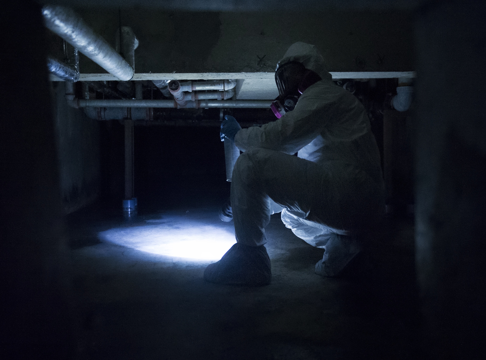 Staff Sgt. Brandon Cenarrusa, 374th Civil Engineer Squadron pest management craftsman inspects the crawlspace of the Child Development Center at Yokota Air Base, Japan, Jan. 6, 2016. To ensure that facilities on Yokota remain pest free, entomology Airmen identify and repair any infrastructure imperfections that may lead to pest. (U.S. Air Force photo by Airman 1st Class Delano Scott/Released)