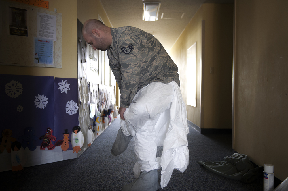 Staff Sgt. Brandon Cenarrusa, 374th Civil Engineer Squadron pest management craftsman, dons a protective suit before entering the crawlspace of the Child Development Center at Yokota Air Base, Japan, Jan. 6, 2016. 374 CES utilize preventative and immediate response maintenance practices to ensure that facilities remain pest free. (U.S. Air Force photo by Airman 1st Class Delano Scott/Released)